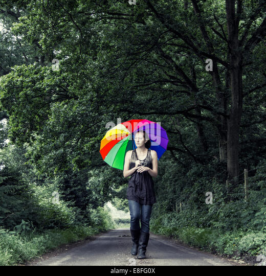 Woman walking down street with multi-colored umbrella - Stock Image
