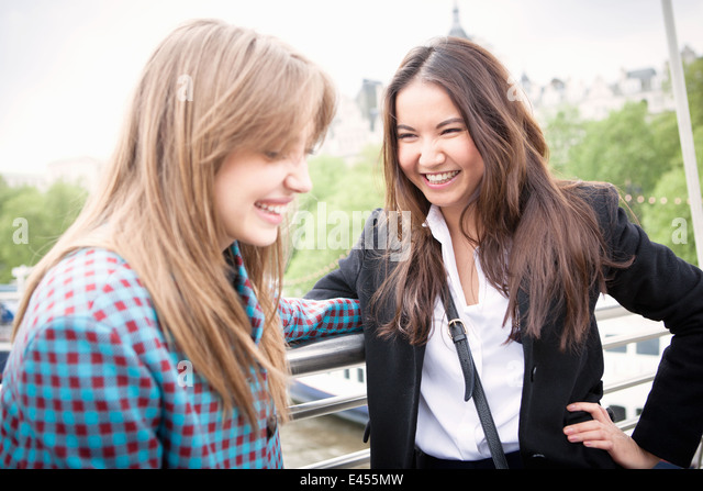 Two young female tourists giggling on Golden Jubilee footbridge, London, UK - Stock Image