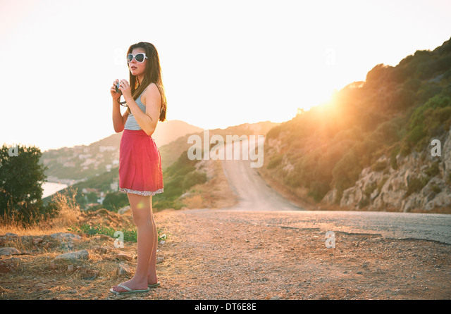 Girl holding camera at sunset, Kas, Turkey - Stock Image