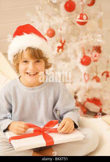 Boy sitting by Christmas tree in a red and white furry hat unwrapping a gift - Stock Image