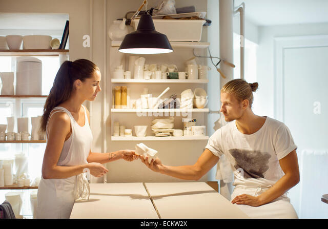 Workers looking at crockery at workshop - Stock Image