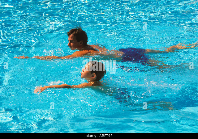 A father gives a swimming lesson to his nine year old son - Stock Image