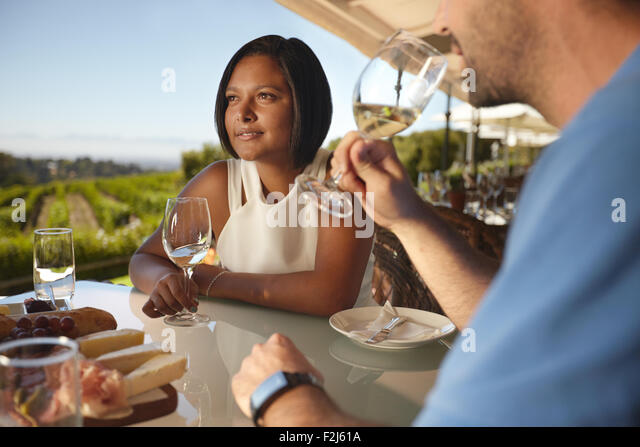Young woman with a man drinking wine. Couple on vacation in outdoor wine bar restaurant by a vineyard. - Stock-Bilder