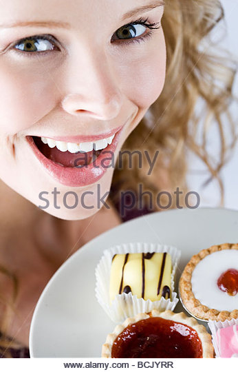A portrait of a young blonde woman holding a plate of assorted cakes, close-up - Stock Image