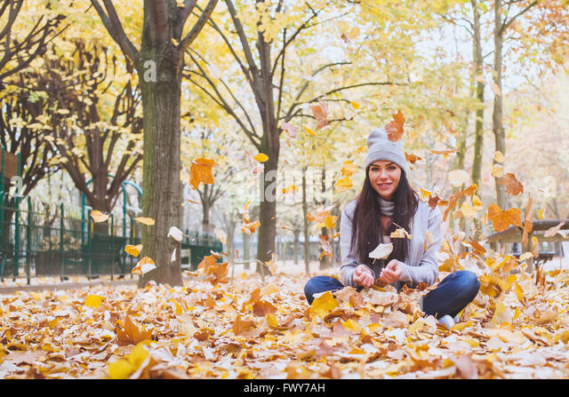 autumn park, beautiful smiling woman and falling yellow leaves - Stock Image