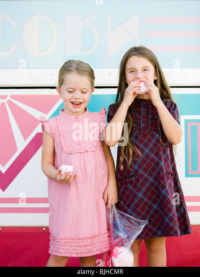 two sisters eating cotton candy at the carnival - Stock Image