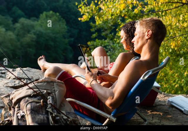 Young couple relaxing on rock ledge, Hamburg, Pennsylvania, USA - Stock-Bilder