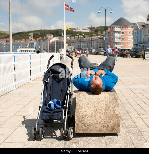 a man lying down on a seaside bench next to an empty kids buggy, aberystwyth wales uk - Stock Image