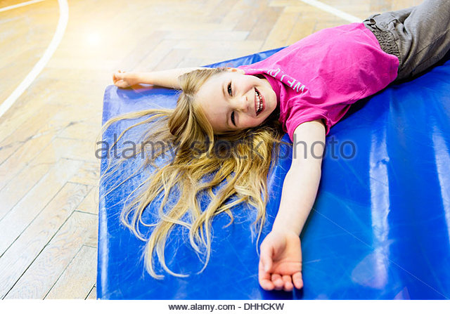 Girl lying on blue exercise mat, smiling - Stock Image