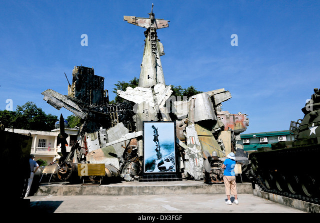 A Tourist looks at the wreckage of captured American planes at the Vietnam military history Museum, Vietnam, South - Stock Image