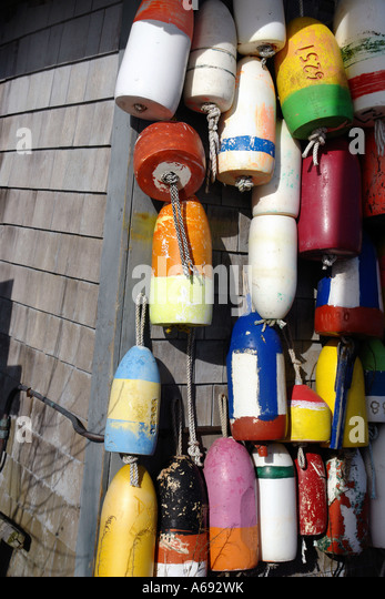 Colorful Nautical Buoys Hanging on The Side Of A Building - Stock Image