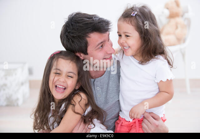 Happy father with daughters spending quality time together at home - Stock Image