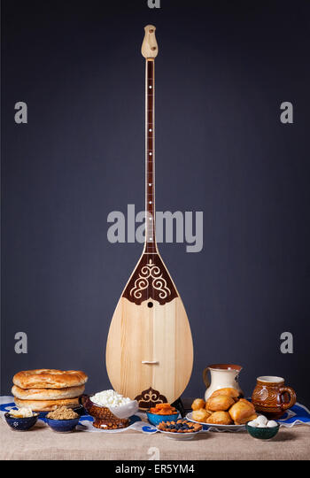 Dombra Kazakh instrument and Asian dishes on the table at grey background - Stock Image