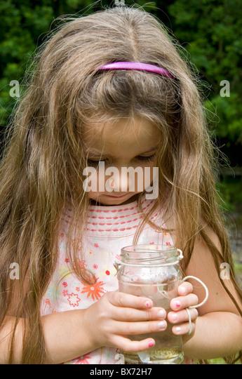 Girl looking at fish caught in jam jar - Stock Image