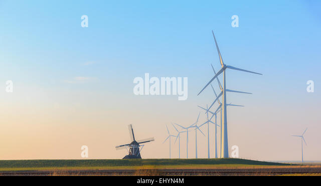 Rows of wind turbines and an old traditional windmill, Eemshaven, Groningen, Netherlands - Stock Image