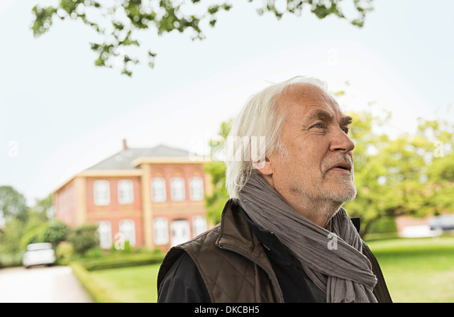 Senior man wearing scarf looking away - Stock Image