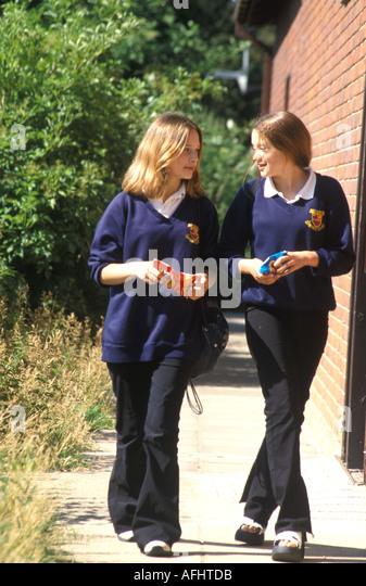 2 teenage girls walking to school eating crisps - Stock Image