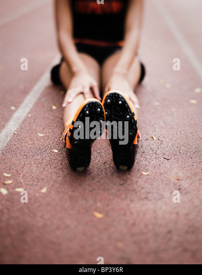 African american sprinter girl stretching legs on a track - Stock Image