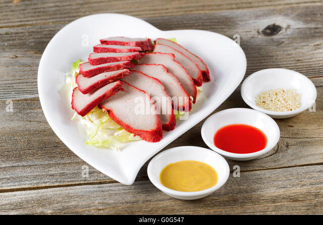 Freshly sliced pork with dipping sauces ready to eat - Stock Image