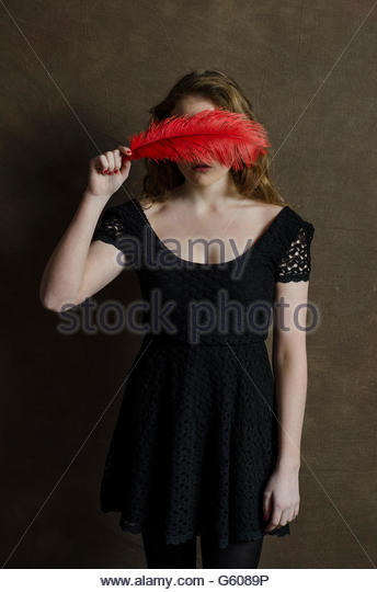 Young woman hiding face with red feather - Stock-Bilder