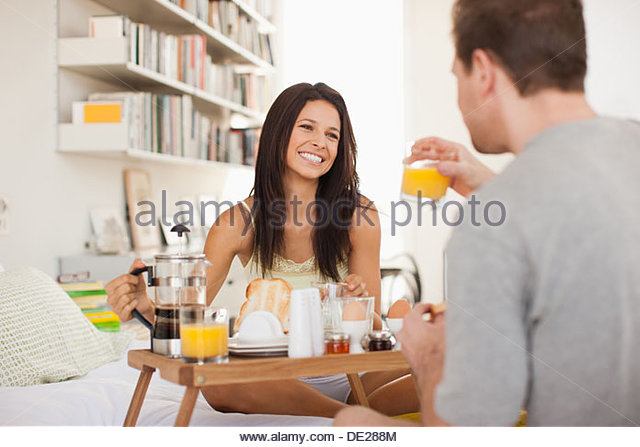 Couple eating breakfast in bed - Stock Image