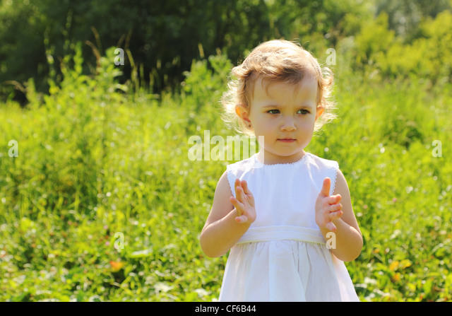 Little girl standing in the grass shows something with her hands - Stock Image