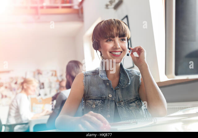 Smiling design professional using headset with microphone in office - Stock-Bilder