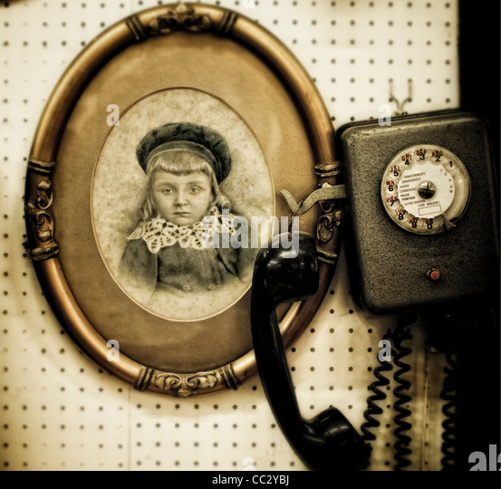 Antique phone and vintage framed photograph of young child - Stock Image