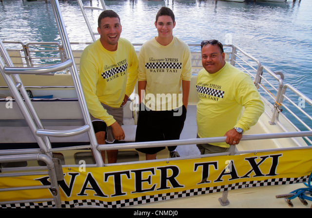 Miami Beach Florida Biscayne Bay Miami Beach Marina Biscayne Xpress Water Taxi boat Hispanic man teen boy guide - Stock Image