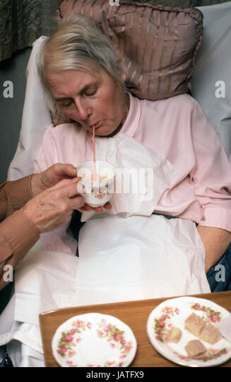 nurse giving woman suffering from late stages of motor neuron disease tea to drink through a straw - Stock Image