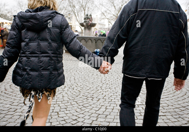 A couple wearing fancy dresses walk in the streets of Cologne during the Carnival Crazy Days in Cologne (Germany) - Stock Image