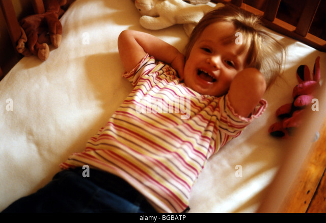 Photograph of child laying in babies cot laughing laugh smile - Stock-Bilder