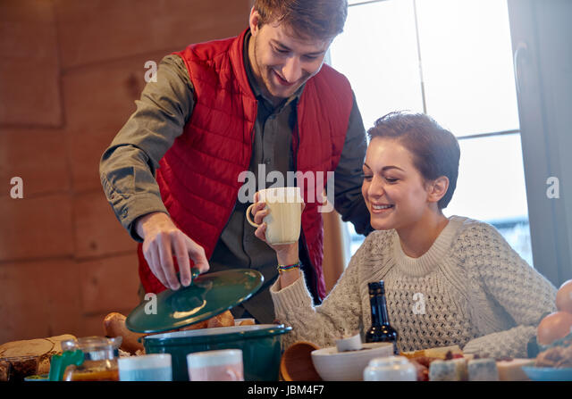 Couple cooking and drinking at cabin table - Stock-Bilder