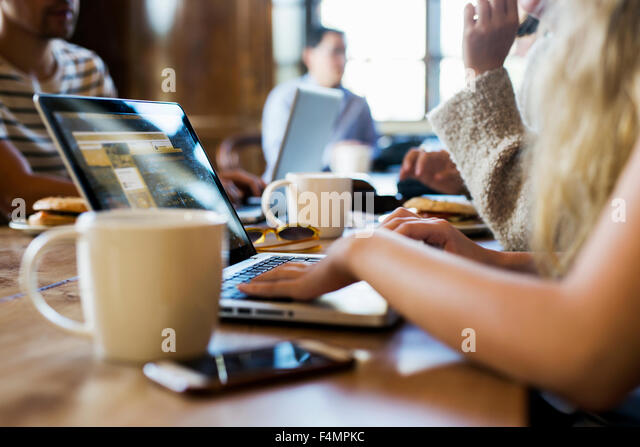 Cropped image of freelancers working on laptop at cafe - Stock-Bilder
