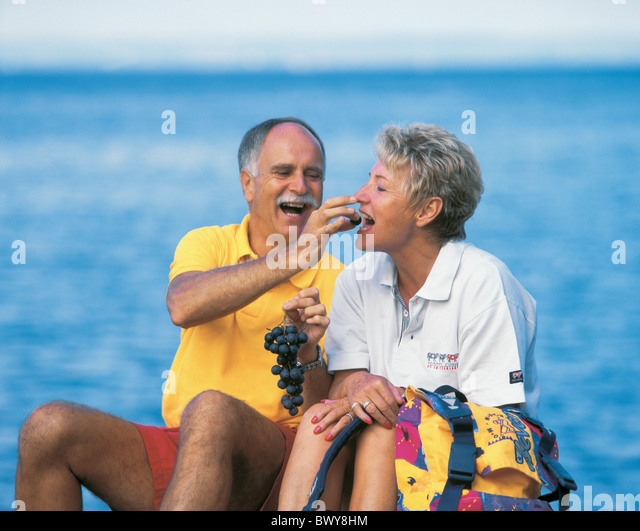 beach couple eating food middle age nature old person outside relax grapes sea seashore seniors sit si - Stock Image