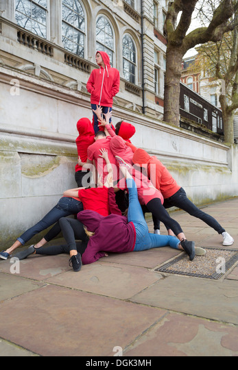 Group of young people performing on city street - Stock Image
