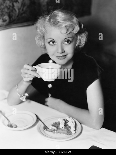 Portrait of woman having pie and coffee - Stock Image