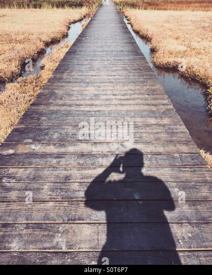 Man silhouette on promenade over lake - Stock Image