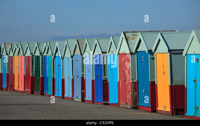 Brighton has rows of colourful beachhuts on the seafront. The doors are painted bright colours. - Stock Image