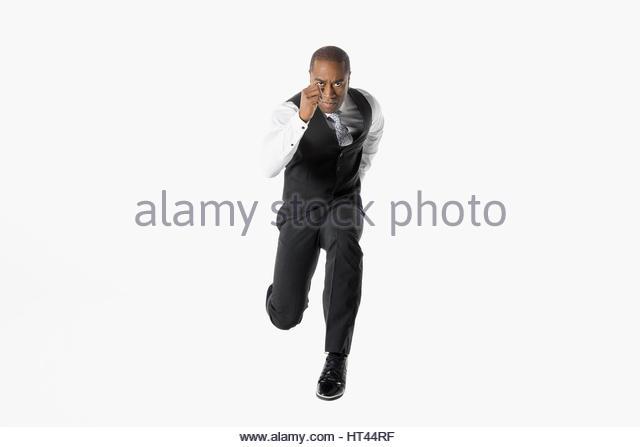 Portrait determined businessman running on the move against white background - Stock-Bilder