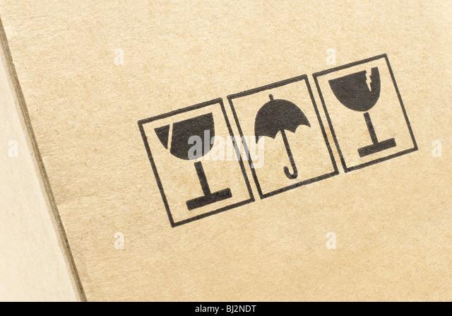 Close up of caution symbols printed on carton box - Stock Image