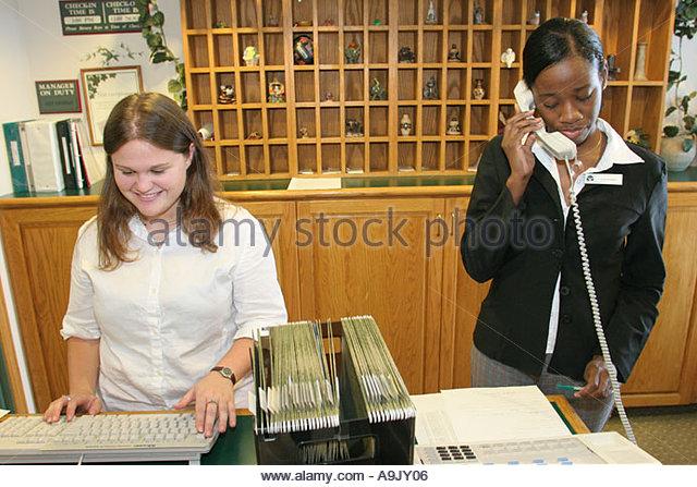 Tuscaloosa Alabama Country Inn and Suites reception desk White Black female employees - Stock Image