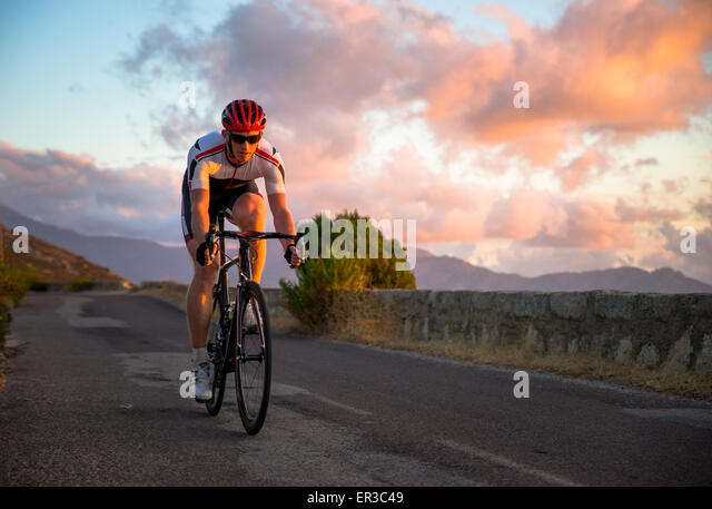 Man cycling at sunset, Corsica, France - Stock Image