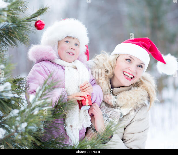 Happy family mother and kid decorating christmas tree outdoor - Stock Image