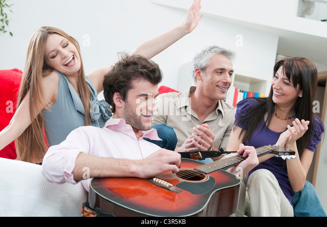 Joyful friends playing guitar at home - Stock Image
