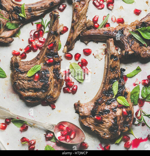 Lamb ribs barbecue with pomegranate seeds and herbs, square crop - Stock Image