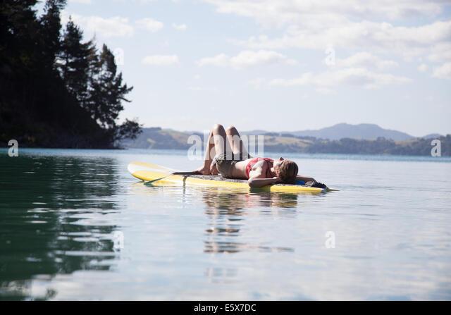 Mid adult woman sunbathing on paddleboard at sea - Stock Image