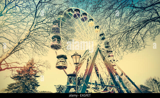 Retro old film faded picture of ferris wheel in a park. - Stock Image