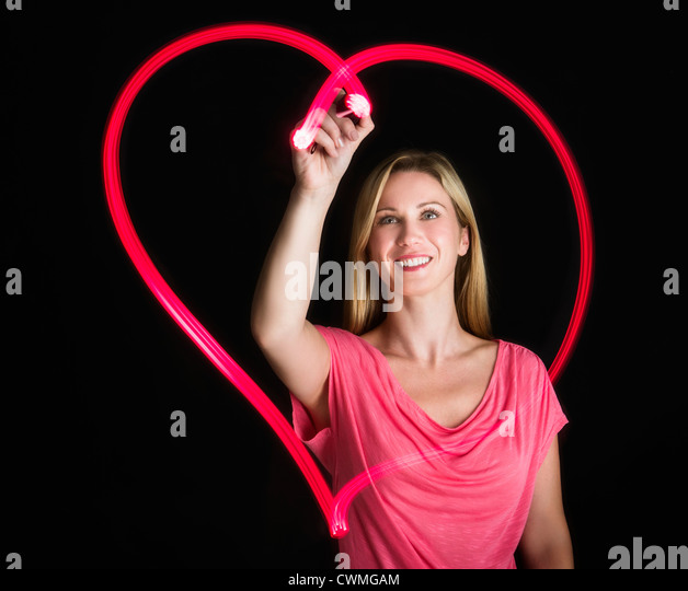 Woman drawing heart on black background - Stock-Bilder