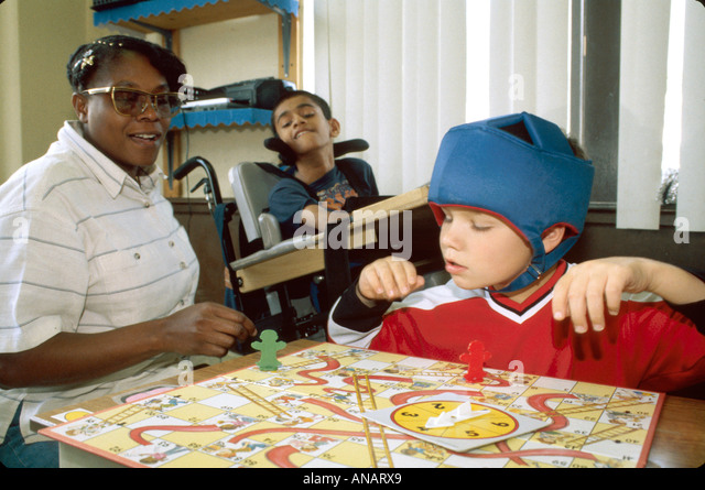 New Jersey East Orange Cerebral Palsy Center disabled student Black female therapist soft helmet boy - Stock Image